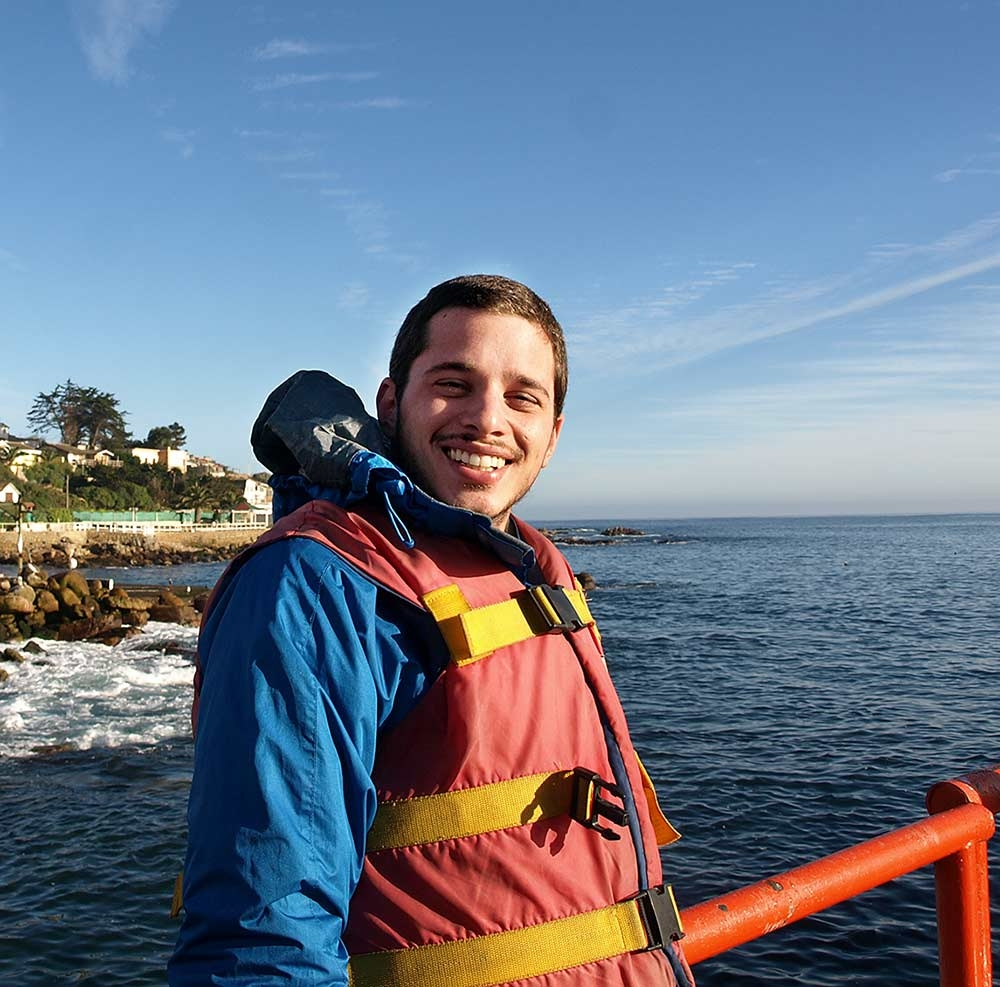 Daniel Viana wears life jacket riding a boat